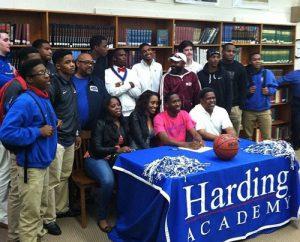Reggie Anthony signing at Harding University surrounded by family. Photo courtesy Harding Sports Info.